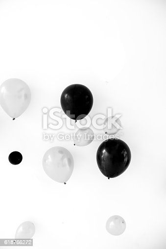 A floating balloon in the air inside a party room with backdrop in the background, in black and white