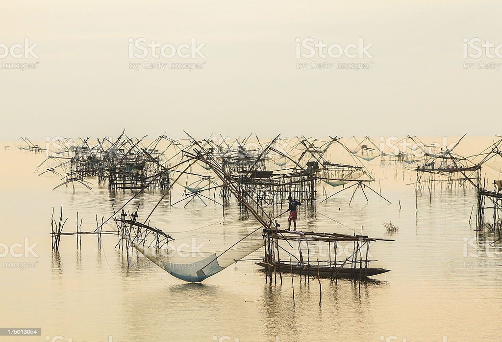 floating basket for keeping live fish in water before sunrise royalty-free stock photo