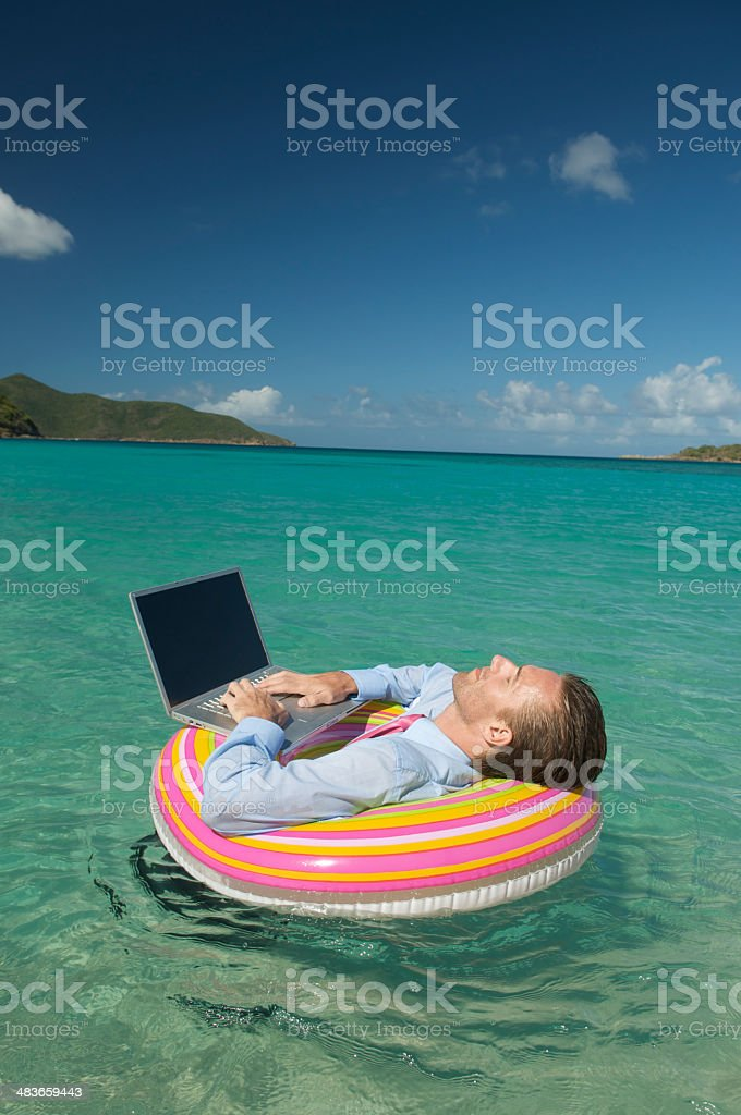 Floating Businessman Does Extreme Daydreaming with Laptop in Sea royalty-free stock photo