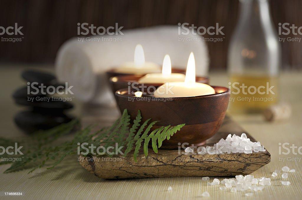 Candele galleggianti in una spa zen di pietre di massaggio e olio