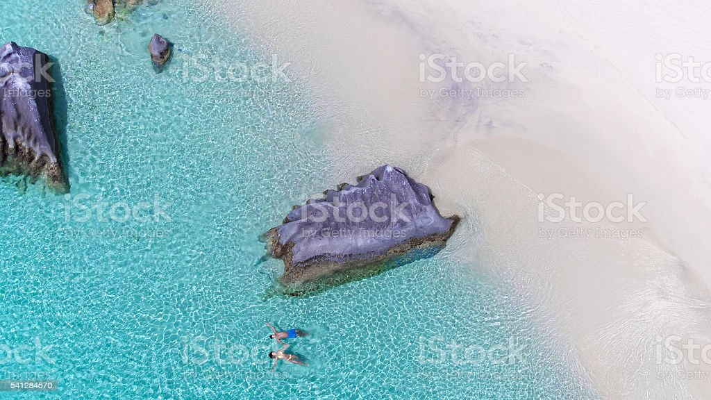 floating couple on perfect beach in Virgin Gorda, BVI stock photo
