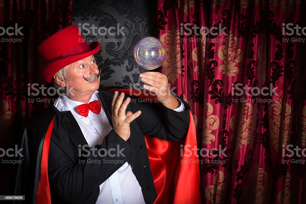 Floating crystal ball and magician stock photo