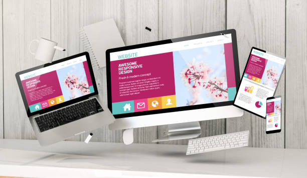 floating devices at the office with awesome responsive homepage on screen stock photo