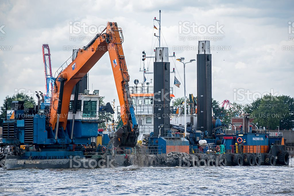 floating dredge deepens the fairway for large container ships stock photo