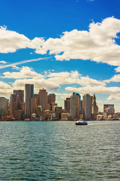 Floating ferry boat with the skyline of Boston in background stock photo