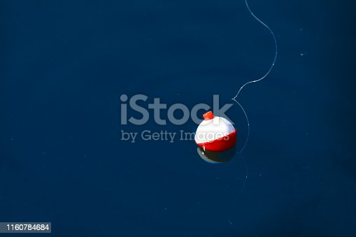 red and white floating fishing bobber with white fish line on dark blue still water