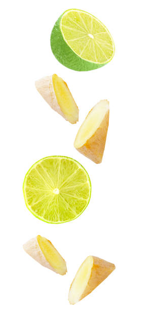 Floating ginger and lime fruit isolated on white stock photo
