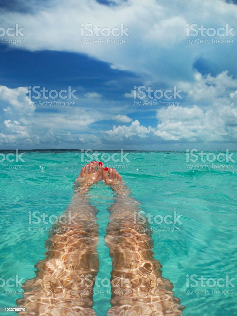 Floating in Clear Blue Ocean A first person perspective of a woman floating in the clear beautiful waters of the Bahamas. Adult Stock Photo