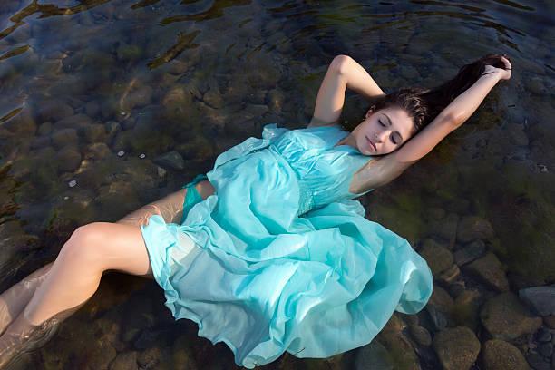 schwimmende in dunklen gewässer - meerjungfrau kleid stock-fotos und bilder