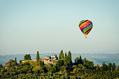 A beautiful Tuscan scene of a hot air ballon floating over a villa