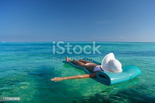 woman floating on a raft in the water at a tropical beach