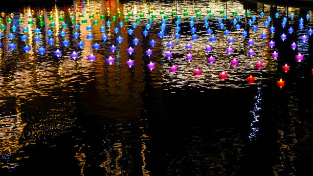 Floating lanterns and colored water reflections stock photo