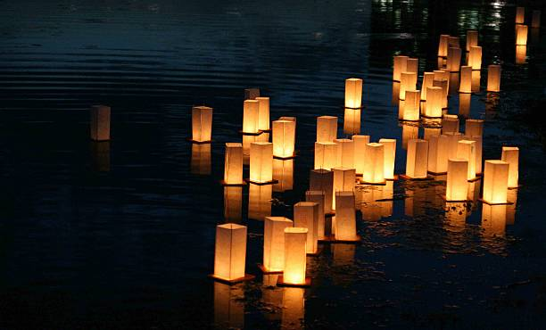 Floating Lanterns Lanterns floating on a lake at dusk. lantern stock pictures, royalty-free photos & images