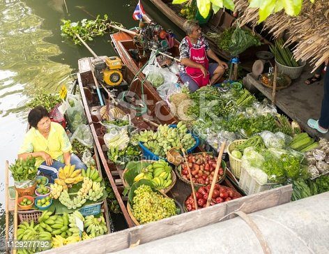 Two vendors in boats wait for customers at the Klong Lat Mayom floating market in Bangkok, Thailand. These and other vendors sell a variety of food, including fruit, vegetables and cooked food, to local people and visitors.