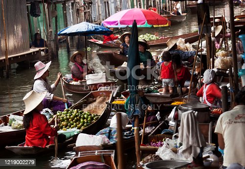 Damnoen Saduak, Thailand-August 9, 2009: People sells souvenirs from his boat at a floating market near Bangkok