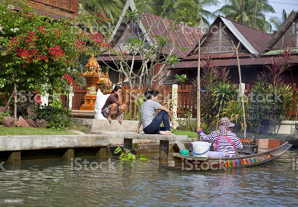 Floating market, thai woman selling skewers from a boat. royalty-free stock photo