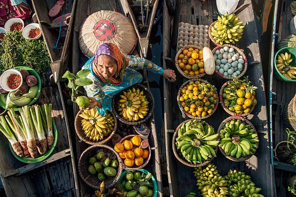 marché flottant non identifiée trader offre goyave fruits frais - indonésie photos et images de collection
