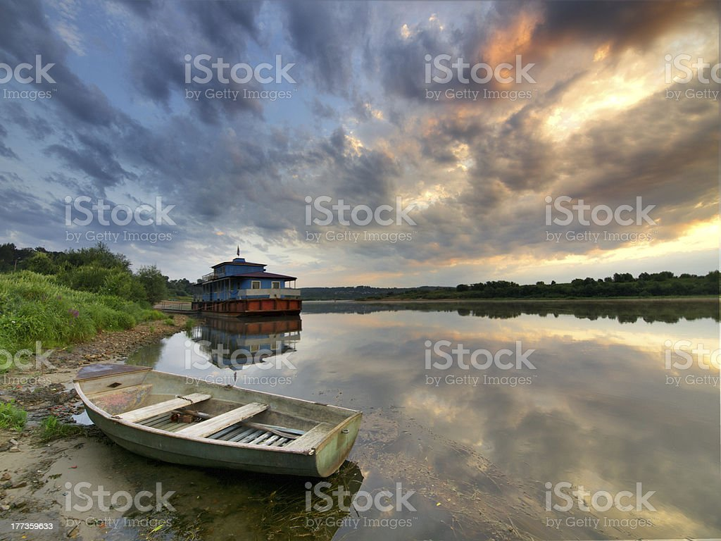 Floating pier and wooden boat on a river at sunrise, stock photo