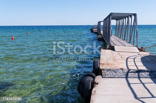 Floating pier on the blue sea background. Travel or vacation destination. Pontoon bridge for boarding ships. Close-up showing detail of ironwork, concrete and wooden walk way that floating