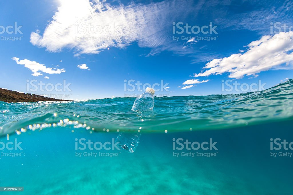 Floating plastic bottle on ocean surface stock photo