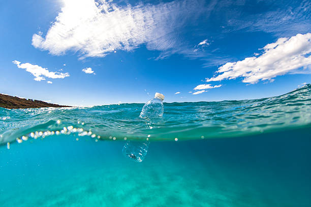 floating plastic bottle on ocean surface - plastic stock pictures, royalty-free photos & images