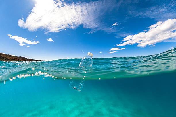 floating plastic bottle on ocean surface - détritus photos et images de collection