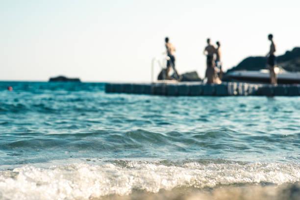 Schwimmende Plattform im Meer, mit Teenagern, die Spaß haben, aus dem Fokus – Foto