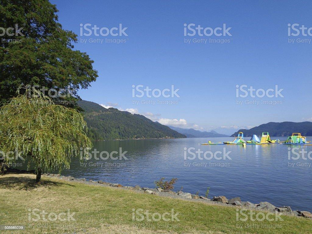 Floating playground on lake against mountains stock photo