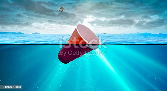 Floating red cup in sea.