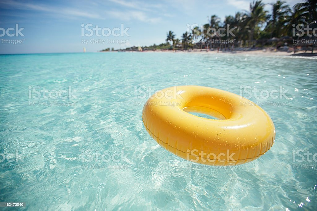 floating ring on blue clear sea with beach, shallow dof stock photo