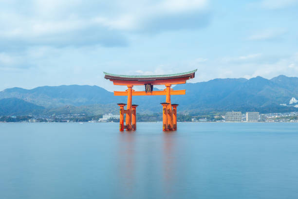 Floating Torii of Itsukushima Shrine in Hiroshima, Japan Itsukushima Shrine is a Shinto shrine on the island of Itsukushima (Miyajima). the floating torii is a recognizable landmark. it looks like floating on the ocean as high tide. shinto stock pictures, royalty-free photos & images