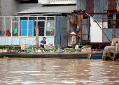 Vegetable boat, Mekong River, South Vietnam. Water craft traffic such as barges, houseboats, passenger craft, industrial freighters and small personal boats travel the green rippled waters of the channels and routes of the mighty Mekong River as it flows to the Mekong Delta, South Vietnam