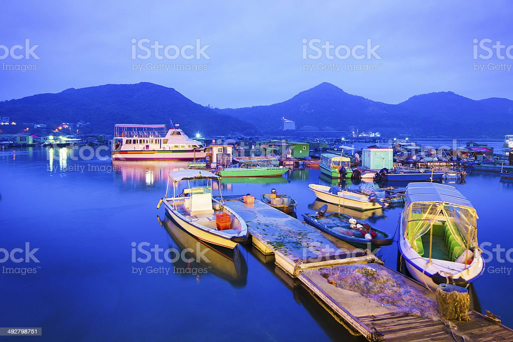 Floating village and moored boats at dusk stock photo