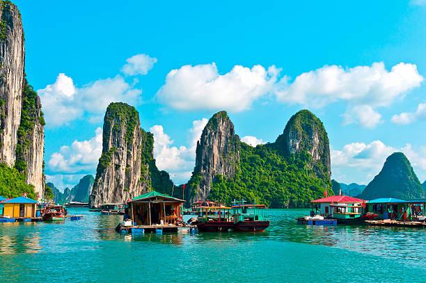Villaggio galleggiante vicino rock islands nella Baia di Ha Long - foto stock