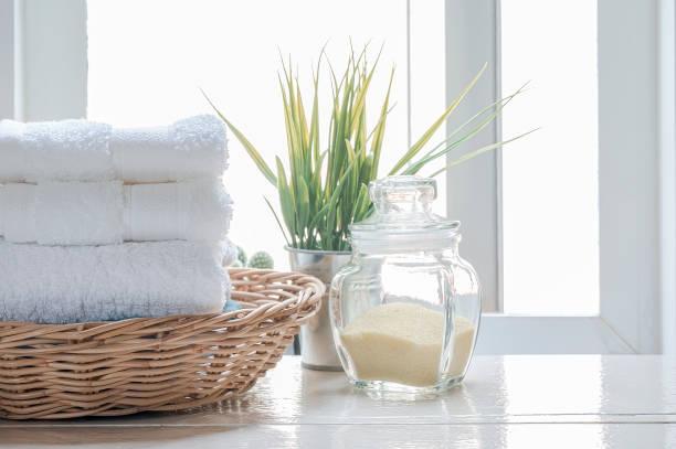 Toallas limpias en cesta de ratán sobre mesa de madera blanca. - foto de stock