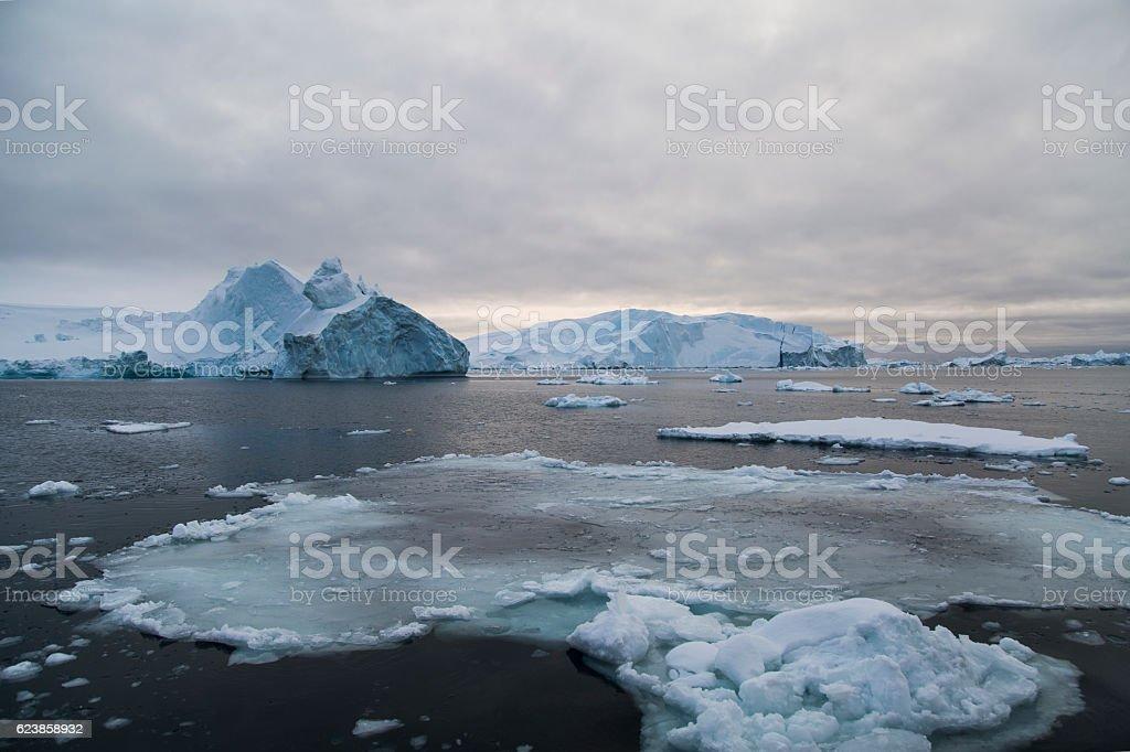floe drifting in dark water with iceberg stock photo