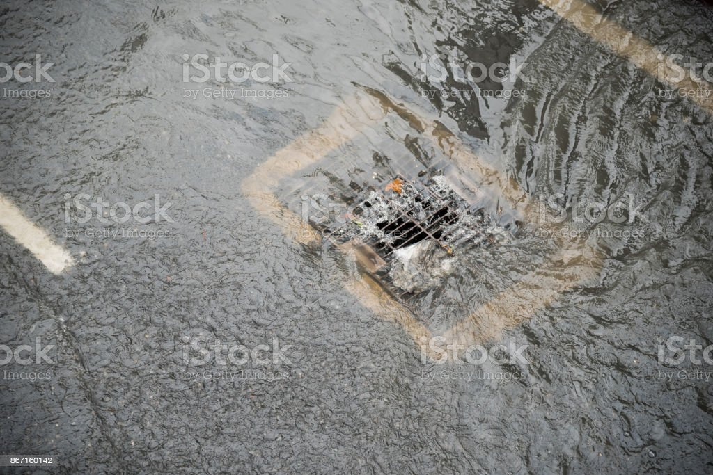 flood after the rain is flowing down the drain on the road stock photo