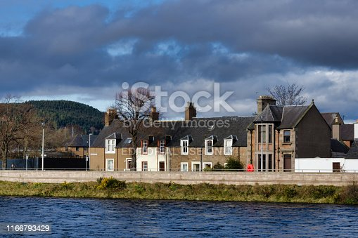 Inverness, Scotland - March 18 2019:  Here we see the River Ness.  A freshwater river flowing through the capital city of the Scottish Highlands.  Along the riverbank are rows of old traditional houses on Shore Street.
