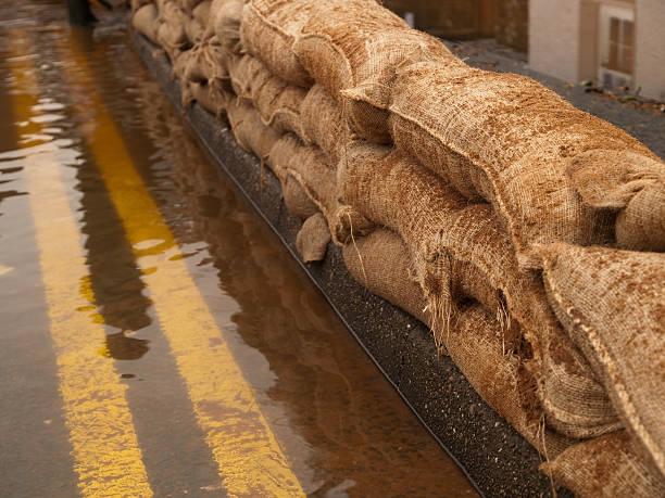 überschwemmung verteidigungsfront - sandsäcke stock-fotos und bilder