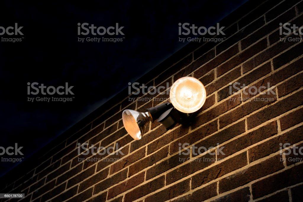 Lumière d'inondation sur la brique extérieure mur nuit chercher - Photo