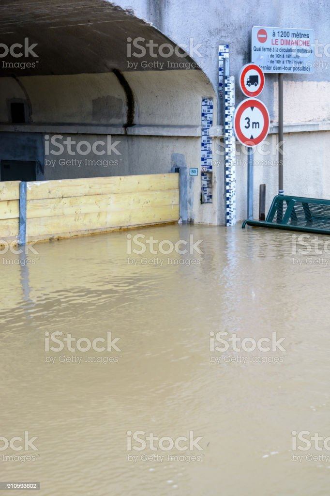 Flood markers and road signs at the entrance of a tunnel flooded by the river Marne. The text on the sign says 'at 1200 meters on Sundays wharf closed to vehicle traffic from 10 to 18 in summer and from 10 to 17 in winter (last U-turn opportunity)'. stock photo
