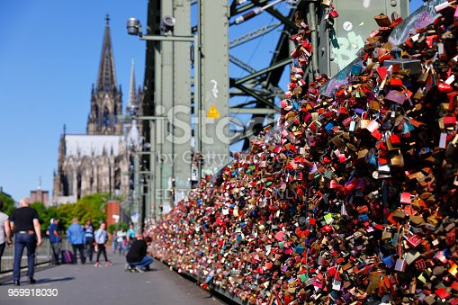 Cologne, Germany - May 06, 2018. Hundreds of thousands love locks mounted at the railing of the Hohenzollern Bridge - accumulated over many years. A few tourists examine the flood of locks.