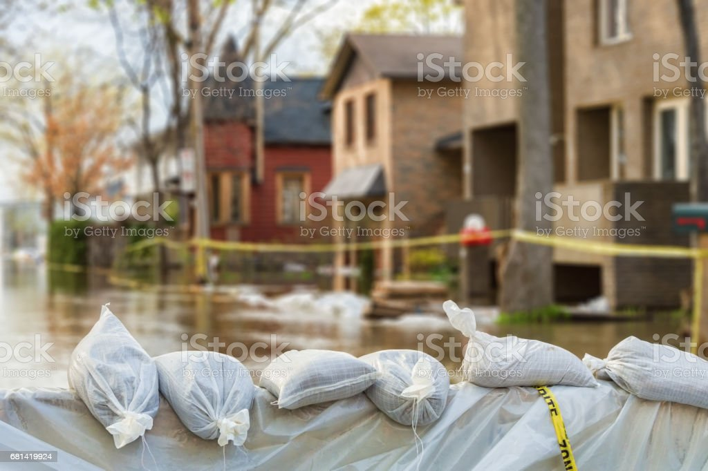 Flood Protection Sandbags with flooded homes in the background stock photo