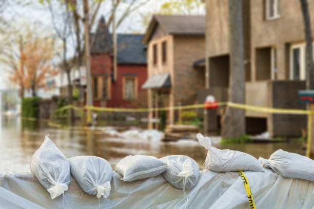 flood protection sandbags with flooded homes in the background - damaged stock photos and pictures