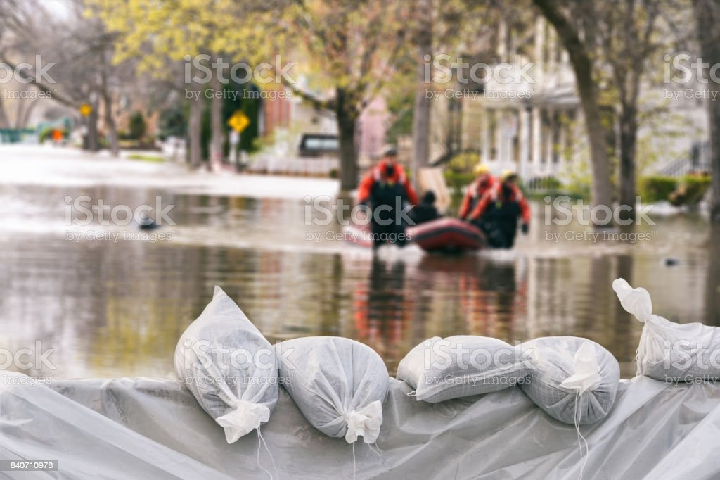 Flood Protection Sandbags with flooded homes in the background (Montage) royalty-free stock photo