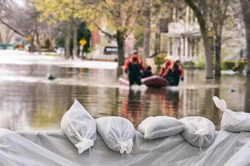 istock Flood Protection Sandbags with flooded homes in the background (Montage) 840710978