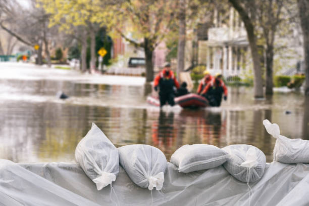 Flood Protection Sandbags with flooded homes in the background (Montage) stock photo