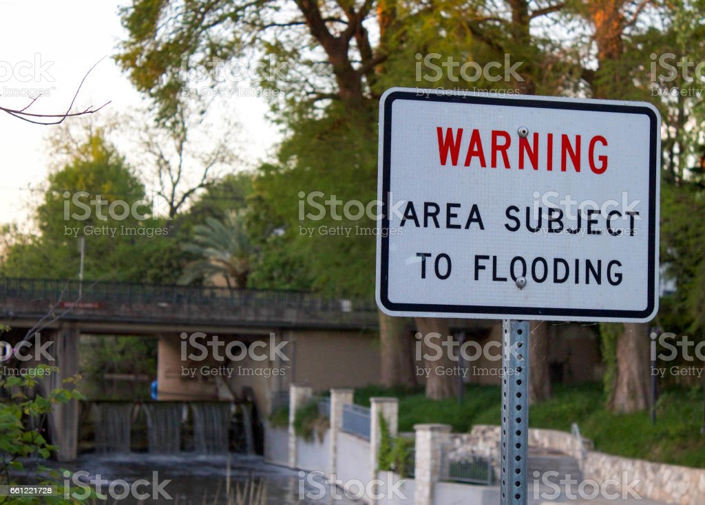 Flood Warning Sign on River Bank stock photo