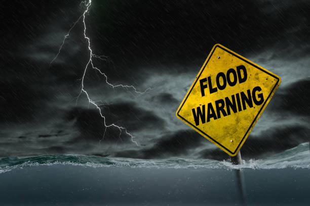 Flood Warning Sign Submerged in Rising Water With Stormy Background stock photo