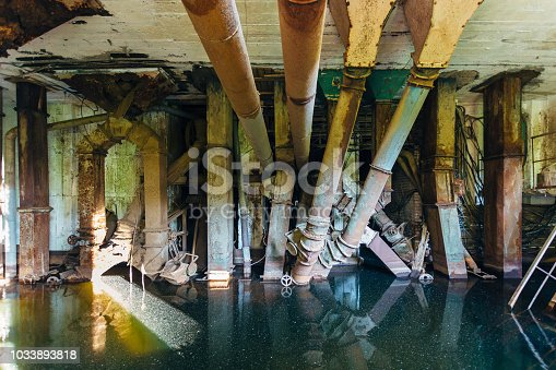 Flooded abandoned ruined factory. Old rusty pipes in dirty water.